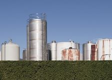 Industrial tanks behind hedge Royalty Free Stock Image