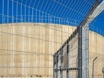 The industrial tanks are enclosed by a high metal fencing against the blue sky. Stock Photos