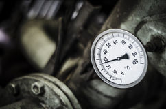 Industrial temperature gauge. With out of focus pipes in background Royalty Free Stock Images