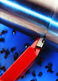 Industrial tool cutting a pipe. A red industrial tool cutting a shinny pipe over a blue background Stock Images