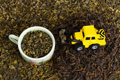Industrial tractor toy load green tea leafs to cup. (installation on the theme of tea business Royalty Free Stock Photo