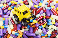 Industrial tractor toy load pills. And tablets (Installation on the theme of modern medicine stock image