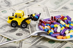 Industrial tractor toy load pills and tablets to plate. (installation on the theme of modern medicine trends stock photo