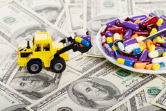 Industrial tractor toy load pills to plate. (installation on the theme of modern medicine trends royalty free stock photo