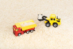 Industrial tractor toy load rice seeds to dump truck. (installation on the theme of agriculture business Stock Images