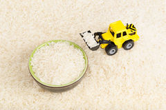 Industrial tractor toy load rice seeds to plate Royalty Free Stock Photo