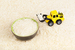 Industrial tractor toy load rice to plate Stock Photos