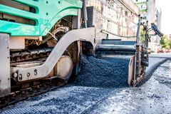 Industrial truck laying fresh bitumen and asphalt Stock Photos