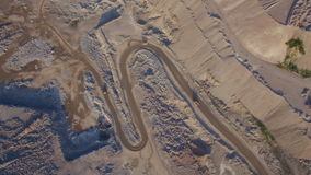 Industrial trucks moves along the road in the sand quarry. Aerial view of Industrial truck moves along the road in the sand quarry. 3 trucks are moving in stock video footage