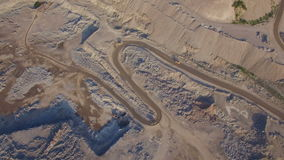Industrial trucks moves along the road in the sand quarry. Aerial view of Industrial truck moves along the road in the sand quarry. 3 trucks are moving in stock video