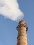 Industrial tube. Steaming old fashioned industrial tube against blue sky Stock Images