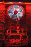Industrial turbine in red light and old pipes. Industrial decoration with old bricks, red light and old pumps, old pipes and turbine. Turbine wheel in old stock image