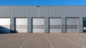Industrial Unit with roller shutter doors. Row of grey industrial Units with roller shutter doors royalty free stock image