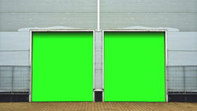 Industrial Unit with roller shutter doors. Warehouse storage doors with green screen mate background are closing. 1920x1080 Stock Photo