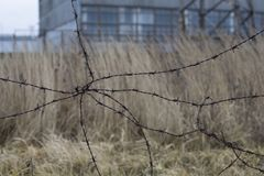 Industrial urban landscape with old barbed wire. Industrial sad autumn urban landscape with abadoned buildings and old barbed wire Stock Photos