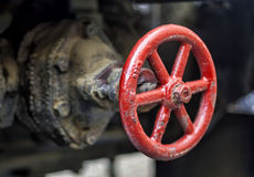 Industrial valve wheel. A grimmy red wheel valve regulating the flow of industial base liquids Stock Photos