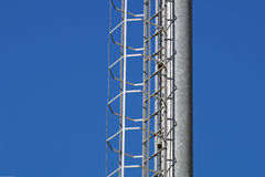 Industrial vertical stairs with blue sky background in high contrast. Royalty Free Stock Photo