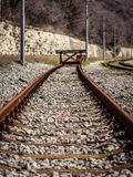 Industrial view of dead end railway track. Wooden sign at the en. D of the rail trail. Concept for end,border and limitation stock photography