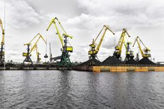 Working crane in the port, The Cargo in the Port Pier at the Loading of Coal. Industrial view. Working crane in the port, The Cargo in the Port Pier at the royalty free stock photo