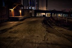 Industrial vintage warehouse alley dock at night. Royalty Free Stock Photo