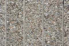 Industrial wall. Concrete wall segments with embedded stones royalty free stock photography