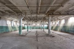 Industrial warehouse with cement walls, floors, windows and pillars before construction, remodeling, renovation. Empty industrial warehouse or commercial area in royalty free stock photography