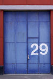 Industrial warehouse exterior with aged blue door and gate. Royalty Free Stock Images