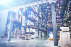 Industrial warehouse and logistics concept. Large storage with racks, shelves, boxes, containers and other goods stock photography
