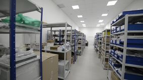 Industrial warehouse. White metal racks with blue plastic trays and cardboard boxes installed in them. stock video