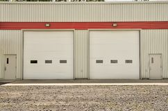 Industrial warehouse with white roller doors. Stock Images