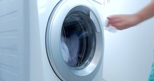 Close up industrial washing machine washes colored clothing and white linen, white striped clothing. Cylinder spinning. Industrial washing machine washes colored stock footage