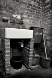 Industrial washroom. Monochrome of old sink with buckets and mops in a basic brick industrial wash room Stock Image