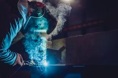 Industrial Welder With Torch. And Protective Helmet in big hall welding metal profiles stock images
