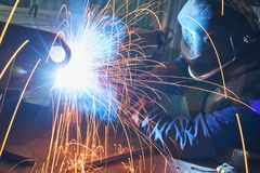 Industrial arc welding work. Industrial welder worker at arc welding process with sparks. Focus on sparkle Royalty Free Stock Photos