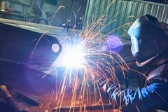 Industrial arc welding work. Industrial welder worker at arc welding process with sparks. Focus on sparkle Royalty Free Stock Image