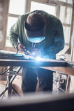 Industrial welder working a welding metal with protective mask Stock Images