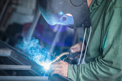 Industrial welder working a welding metal with protective mask Stock Photography