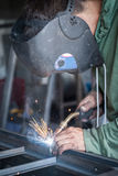 Industrial welder working a welding metal with protective mask Royalty Free Stock Images
