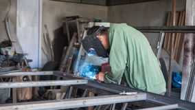 Industrial welder working a welding metal with protective mask Stock Photo