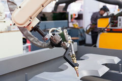 Industrial welding robot arm. In the focus, blurred welder in the background Royalty Free Stock Images