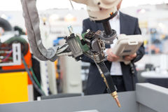 Industrial welding robotic arm, blurred operator in the background Royalty Free Stock Images