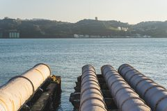 Industrial white pipes feeding into the tagus river, Lisbon, Portugal royalty free stock image