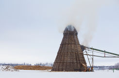 Industrial wood chip burner. A tall coned sawmill wood chip burner with smoke coming out connected to a conveyor with cut logs in the background stock image
