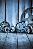 Industrial Cogs Wood Iron Background. Old cogs with a wood floor and corrugated iron background Stock Photography