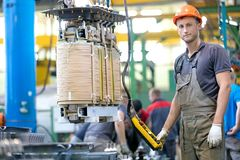 Industrial worker assembling power transformer at conveyor factory workshop royalty free stock photography