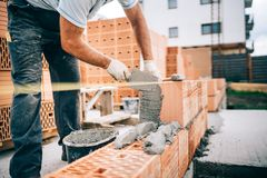 industrial worker, bricklayer installing bricks on construction site stock images