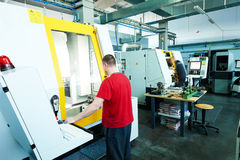 Industrial worker at cnc milling machine cente Royalty Free Stock Image
