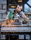 Industrial worker cutting metal Stock Images