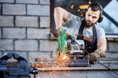 Industrial worker cutting metal. With many sharp sparks working on compound mitre saw with circular blade Royalty Free Stock Photography