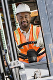 Industrial Worker Driving Forklift At Workplace. Portrait of a happy male industrial worker driving forklift at workplace Stock Image